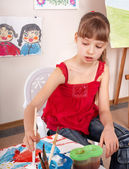 Child with picture and brush in playroom. — Stock Photo
