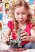Kind vormen uit klei in de speelkamer. — Stockfoto