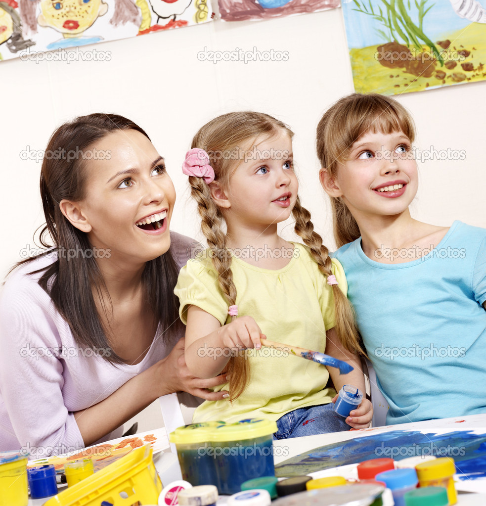 Children painting in preschool. Teacher help by little girl.  Stock Photo #5972959
