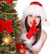 Christmas girl in santa hat making silence gesture. - Lizenzfreies Foto