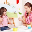 Child with teacher draw paints in play room. — Stock Photo #6101852