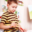 Stock Photo: Little boy with brush draw red sun in play room.