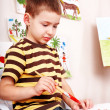 Little boy with brush draw red sun in play room. — Stock Photo #6101867