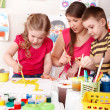 Children painting with teacher. — Stock Photo #6101874
