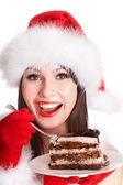 Christmas girl in santa hat eat cake . — Stock Photo