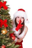 Christmas girl in santa hat making silence gesture. — Stock Photo