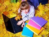 Kid in autumn orange leaves with laptop. — Stock Photo