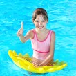 Child sitting on inflatable ring thumb up. — Stock Photo #6140167