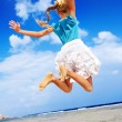 Child playing on beach aganist blue sky. - Stock Photo