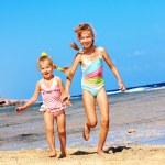 Kids holding hands running on beach. — Stock Photo #6140213