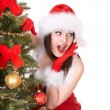 Girl in santa hat near  christmas tree. — Foto de Stock