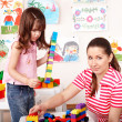 Child with wood block and construction set in play room. — Stock Photo