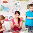 Group child and teacher mould from clay in play room. - Stock Photo