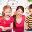 Children with teacher in play room. — Stock Photo