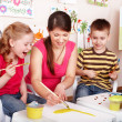 Children with teacher draw paints in play room. - Stock Photo