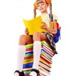 Schoolgirl sitting on pile of books. — Stock Photo #6140458