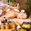 Woman getting thai herbal compress massage . - Stock Photo