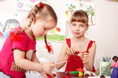 Child mould plasticine in playroom. — Stock Photo