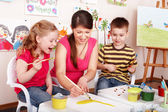 Children with teacher draw paints in play room. — Foto Stock