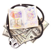 Medical still life with stethoscope, money and passport. — Stock Photo