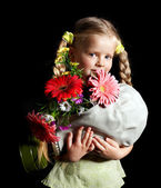 Child holding flowers and gas mask . — Stock fotografie