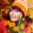 Royalty-Free Stock Photo: Girl in autumn orange hat on leaf group with flower.