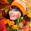 Girl in autumn orange hat on leaf group with flower. - Stock Photo