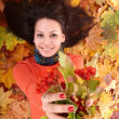 Stock Photo: Girl in autumn orange leaf group with berry.