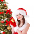 Girl in santa hat decorete christmas tree. - Stockfoto