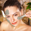 Young woman  having clay body mask. - Stock Photo