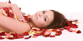 Girl in rose petal. Spa resort. — Stock Photo