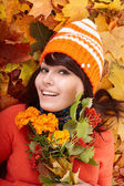 Girl in autumn orange hat on leaf group with flower. — Stock Photo