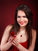 Girl with jewellery box on red background. — Stock Photo