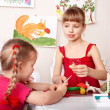 Kids mould plasticine in playroom. - Stock Photo