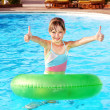 Foto Stock: Child sitting on inflatable ring thumb up.