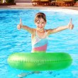 Foto de Stock  : Child sitting on inflatable ring thumb up.