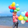 Kid playing with balloons at the beach — Stock Photo