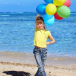 Child playing with balloons at the beach — Stock Photo