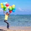Child playing with balloons at the beach — Stock Photo #6336683