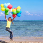 Ребенок, играющий с шарами на пляже — Стоковое фото