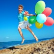 Child playing with balloons at the beach — Stockfoto #6336692