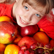 Child girl in group of fruit. - Stock Photo