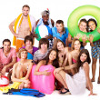 Group holding beach accessories. - Stock Photo