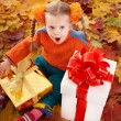 Child  in autumn orange leaves and gift box. — Stock Photo