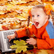 Royalty-Free Stock Photo: Girl child in autumn orange leaves with laptop.