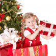 Child giving gift box by christmas tree. — Stockfoto
