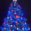 Christmas tree with light and blue star. — Foto de Stock