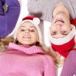 Girls in santa hat lying head next to head. — Stock Photo #6724938