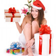 Christmas girl in santa hat, flower, gift box in spa. — Stock Photo