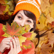 Young woman in autumn orange leaves. - Stock Photo
